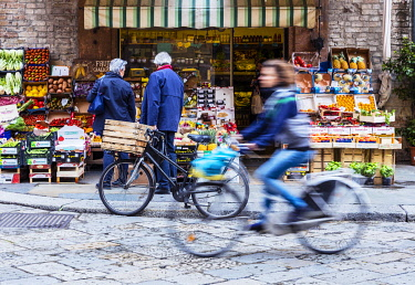 ITA14474 Italy. Emilia Romagna. Parma. A cyclist in the historic centre of Parma in front of a shop selling vegetables.