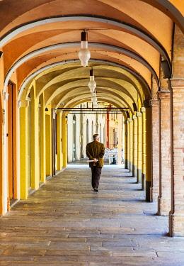 ITA14514 Italy. Emilia Romagna. Reggio Emilia. An elderly man walking under colonnaded arches in the historic centre of Reggio Emilia.
