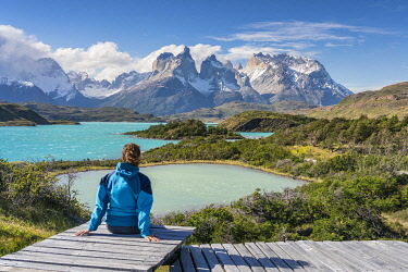 CLKFV106609 Woman sitting on a boardwalk with Lake Pehoé and Paine Horns in the background, on a windy summer day. Torres del Paine National Park, Ultima Esperanza province, Magallanes region, Chile.