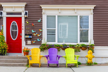 CLKFV111677 Wooden colorful dechchairs in front of traditional house in St John's downtown, Newfoundland, Canada