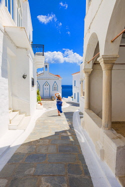 CLKGA106121 Young woman walking on the street that leads to the Church of St. Barbara, Andros, Cyclades archipelago, Greece, Europe (MR)