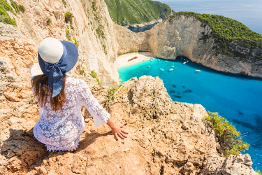 CLKGA107343 Young woman with a straw hat admiring the famous Shipwreck beach of Zakynthos from an elevated place, Ionian Islands, Greece, Europe (MR)