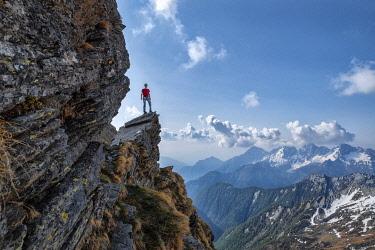 CLKEB111862 Climber on top of rocks at passo Fugiana, Valchiavenna, Valtellina, Sondrio province, Lombardy, Italy