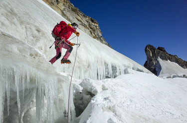 CLKEB111902 Mountaineer on ice jumps the final crevasse before reaching the Gran Paradiso peak, Aosta Valley, Italy