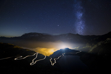 CLKGA95006 Car trails on the winding road leading to Nivolet Pass and milky way in the background, Ceresole Reale, Graian Alps, Gran Paradiso National Park, Piedmont region, Italy