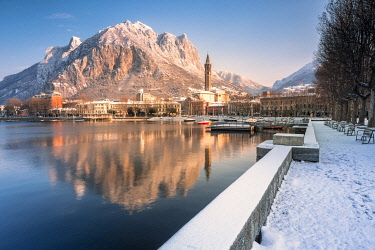 CLKGA95274 Snowy lakefront of Lecco and San Martino Mountain reflected in Como lake, Lecco province, Lombardy, Italy