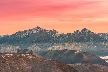 CLKGA105788 Overviewed of Grigna settentrionale and Grigna meridionale peaks from Bollettone Mount and colourful sunrise sky in the background, Como province, Lombardy, Italy
