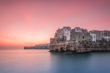 CLKGA95522 Old town of Polignano a Mare built on rocky cliffs at sunrise, Bari province, Apulia region, Italy