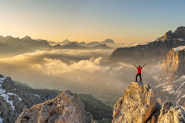 CLKMK112117 Gran Cir, Gardena Pass, Dolomites, Bolzano district, South Tyrol, Italy, Europe. A mountaineer admires the sunrise at the summit of the Gran Cir (MR)