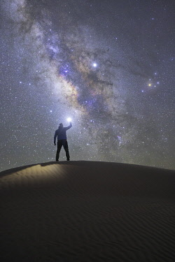 CLKCC110884 Person admiring the milky way in the sand dunes, Sahara desert, Tunisia, Northern Africa.
