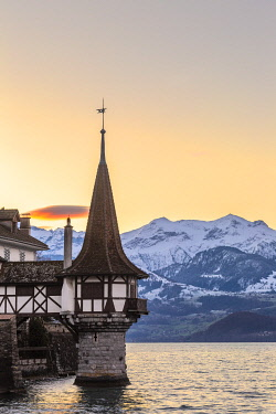 CLKFB103655 Sunrise at the castle of Oberhofen am Thunersee with the snow-covered Bernese Alps in the backgound, Canton of Bern, Switzerland, Europe.