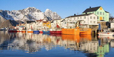 CLKFV107574 Fishing boats in the harbour, with snowcapped mountains in the background. Henningsvaer, Nordland county, Northern Norway region, Norway.