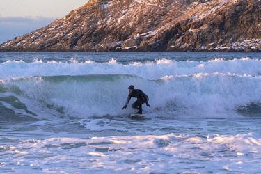 CLKFV107784 Man surfing at Unstad Beach in winter. Vestvagoy municipality, Nordland county, Northern Norway, Norway.