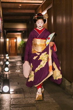 JAP1848AW Young Maiko in kimono walking along an alley at night, Gion district, Kyoto, Japan