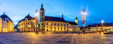 ROM1538AW Piata Mare and the Holy Trinity Roman Catholic Church at dusk. Sibiu, Transylvania. Romania