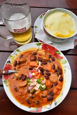 ROM1575AW Traditional pork goulash prepared with hot sausages and red beans and traditional romanian corn meal (mamaliga) served with minced cheese, served piping hot from the oven. Sighisoara, Transylvania. Ro...