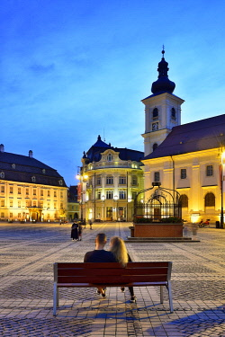 ROM1641AW Moment of peace. Piata Mare and the Holy Trinity Roman Catholic Church at dusk. Sibiu, Transylvania. Romania