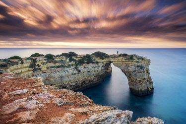 POR10756AW Person on Natural Sea Arch, Praia da Albandeira, Algarve, Portugal