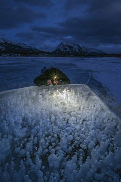 CN01YCH0017 Canada, Alberta, Abraham Lake. Man photographing methane bubbles on frozen lake. (MR)