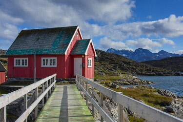 GR01IHO0161 Greenland. Itilleq. Wooden bridge leading to a red house.
