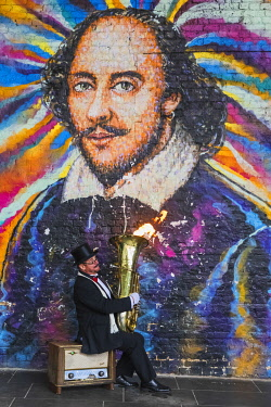 TPX71490 England, London, Southwark, Bankside, Street Musician Playing Fire blowing Tuba in Front of William Shakespeare Mural