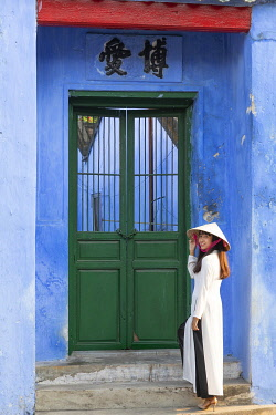 VIT1732AWRF A Vietnamese woman wearing an Ao Dai dress stands in front of an old colonial building in Hoi An Ancient Town, Hoi An, Quang Nam Province, Vietnam
