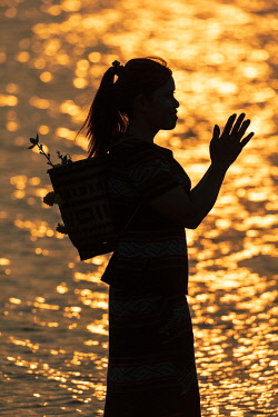 VIT1743AW A M'Nong girl prays at sunset on Lak lake, Dak Lak Province, Vietnam,