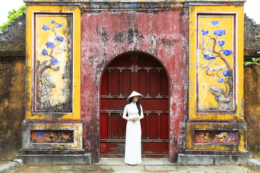 VIT1755AW A Vietnamese girl in an Ao Dai dress stands in front of a historical gate in Hue Imperial Citadel, Hue, Thua Thien-Hue province, Vietnam
