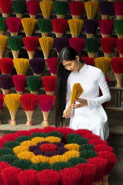 VIT1756AW A Vietnamese woman holds colourful incense sticks in a shop, Hue, Thua Thien-Hue province, Vietnam