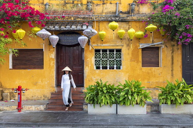 VIT1764AW A Vietnamese girl walks towards a colonial building in Hoi An Ancient Town, Hoi An, Quang Nam Province, Vietnam