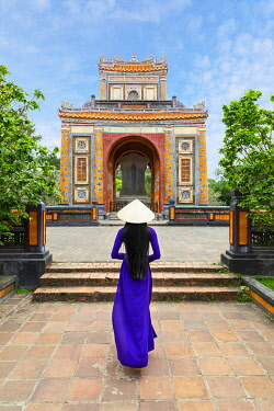 VIT1770AW A Vietnamese woman in an Ao Dai dress walks towards the Tu Duc Tomb, Hue,  Hue, Thua Thien-Hue province, Vietnam