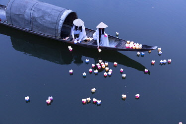 VIT1771AW Vietnamese girls in Ao Dai dresses drop floating candles on a river in Hue to pray for the dead, Hue, Thua Thien-Hue province, Vietnam