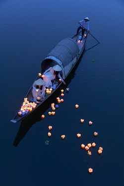 VIT1773AW Vietnamese girls in Ao Dai dresses drop floating candles on a river in Hue to pray for the dead, Hue, Thua Thien-Hue province, Vietnam