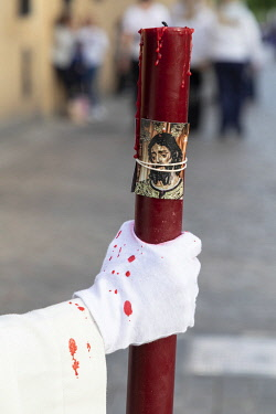 SPA9580AW A penitent holds a large red candle with an image of Jesus duringSemana Santa (Holy Week), Cordoba, Andalucia, Spain