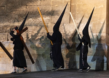 SPA9582AW Penitents in black costumes and conical hats walk past the Cathedral at night during the Semana Santa (Holy Week), Cordoba, Andalucia, Spain