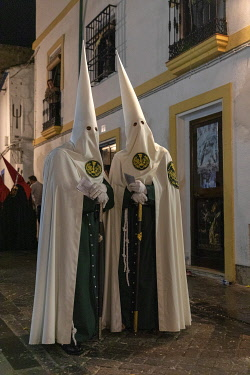 SPA9573AW Penitents in conical hats called Capirotes lead a procession with a throne of the virgin Mary lit by candles through the streets of old Cordoba, Semana Santa (Holy Week), Cordoba, Andalucia, Spain