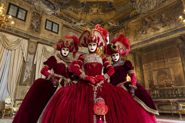 ITA14805AW Three models pose in the music room of the Ca Sagredo Palace, Venice Carnival , Venice , Veneto, Italy