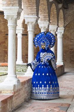 ITA14808AW A model in a colourful costume stands in the cloisers of San Francesco della Vigna, Venice Carnival , Venice , Veneto, Italy