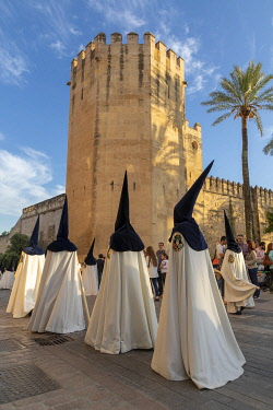 SPA9550AWRF Penitents in conical hats walk past the Royal Botanical gardens during the Semana Santa (Holy Week), Cordoba, Andalucia, Spain