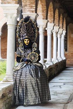 ITA14784AWRF A model in a colourful costume stands in the cloisers of San Francesco della Vigna, Venice Carnival , Venice , Veneto, Italy