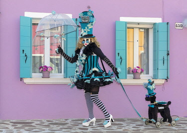 ITA14787AWRF A lady in a lavish costume walks her pretend dog on Burano during the Venice Carnival , Venice, Veneto, Italy