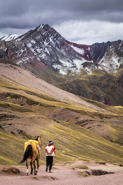 PER34350AW Peruvian horseman walking with horse at Rainbow Mountain, Cusco Region, Peru