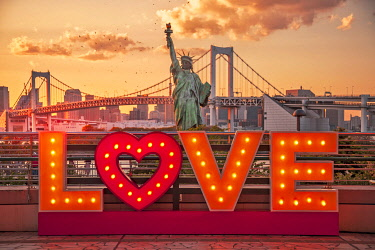 "JAP2030 A ""Love"" art installation looking towards the Odaiba Statue of Liberty Replica and Tokyo's Rainbow Bridge at sunset, Daiba, Tokyo To, Japan."