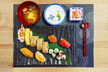 JAP2038 Traditional Japanese Sushi cuisine comprising miso soup, wasabi, ginger, shrimp sushi, tamagoyaki egg roll, Califonia roll, hosomaki, banana leaf and inari age served in traditional style, prepared in...