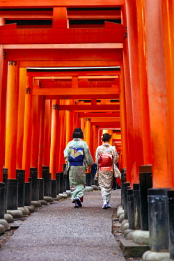 JAP2076 Two Japanese women in traditional costumes stroll through multiple torri (Senbontorii) gates forming the route through the Shinto Fushimi Inari Taisha Shrine, Fukakusa, Shimoseya, Kyoto Fu, Japan.
