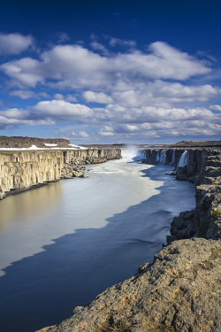 ICE4129AW Scenic view of Selfoss waterfall amidst rocky cliffs against cloudy sky, Northeast Iceland, Iceland