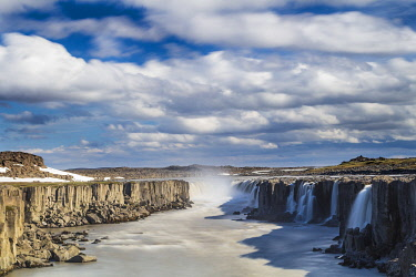 ICE4130AW Scenic view of Selfoss waterfall amidst rocky cliffs against cloudy sky, Northeast Iceland, Iceland