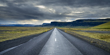 ICE4134AW Straight empty road leading towards mountains against cloudy sky, South Iceland, Iceland
