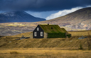 ICE4138AW House with roof covered by grass against mountains, South Iceland, Iceland