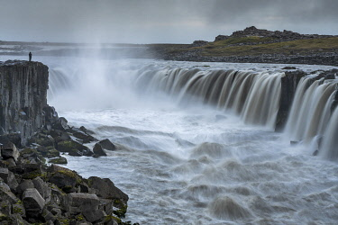 ICE4149AW Tourist standing on cliff at Selfoss waterfall, Northeast Iceland, Iceland